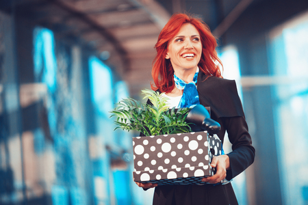Happy businesswoman celebrating success in office district with a box full of her personal belongings from the office just after she give up job.