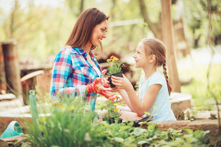 Happiness cute little girl assisting her smiling mother planting flowers in a backyard. Stock Photo