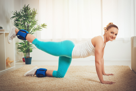 Beautiful young muscular smiling woman doing exercise for a legs at flat. Looking at camera.  스톡 콘텐츠
