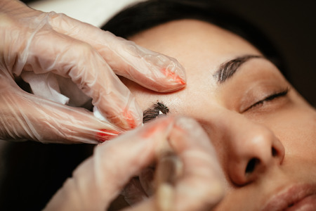 Close-up of a beautician hands microblading eyebrows to model.   Stock Photo