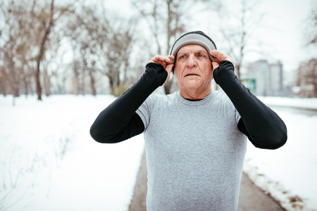 Active senior making pause, puts a hat on the had, during stretching and doing exercises in public park during the winter training outside in. Copy space. Stock Photo