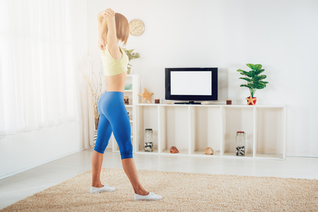 Fit woman warming up while doing stretching exercises at home in front of TV. Archivio Fotografico