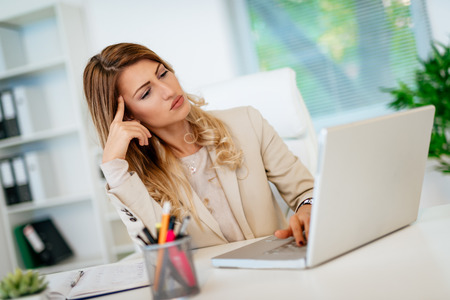 Young pensive business woman thinking about the best possible solutions, while working on her laptop in the office. Stock Photo