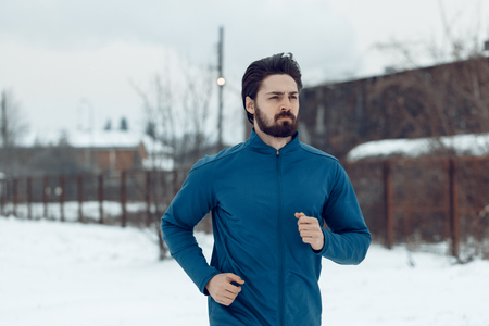 Active young man running and doing exercises in the public place during the winter training outside in. Copy space. Stock Photo - 97870039