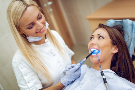 Beautiful young smiling woman at visit in the dentist office and dentist finishing repair tooth with dental curing UV lamp.