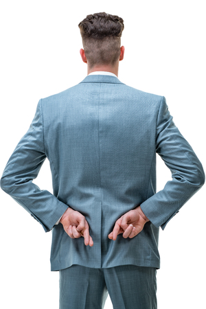 Rear view of a handsome man holding his fingers crossed behind his back, hoping for a positive outcome, isolated on white background.