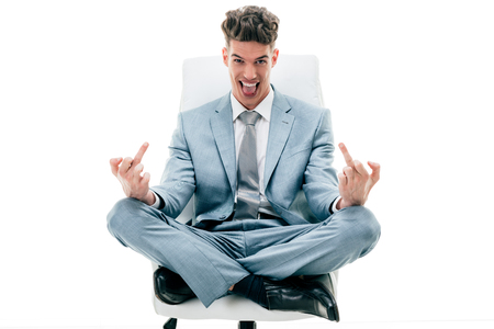 Businessman sitting on an office chair and showing obscene gestures, flipping middle fingers. Isolated on white background.