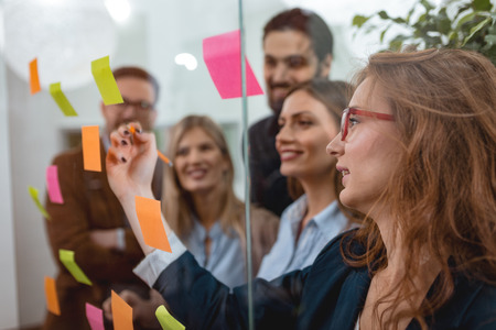 Creative professionals standing and discussing at the office behind glass wall with sticky notes and looking a post it note wall. Stock Photo