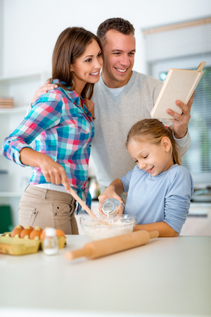 Little girl is pouring the milk in the dish with dough which mother mixing, and father is reading recipe for making cookies in the domestic kitchen. Banque d'images
