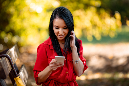 Happy young woman reading message on smartphone in autumn nature.