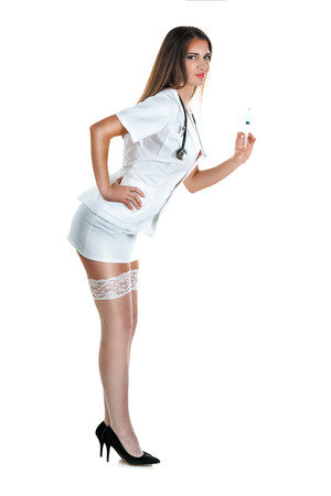 Beautiful smiling sexy nurse with stethoscope and injection in her hand, standing and posing in short skirt and stockings thigh high. Isolated on white background. Looking at camera.
