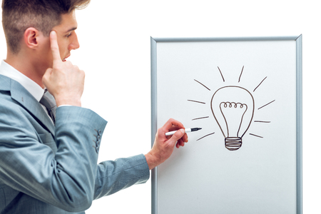 Portrait of handsome young business man having creative idea and drawing light bulb, holding a finger on his blind spot, isolated on white background.