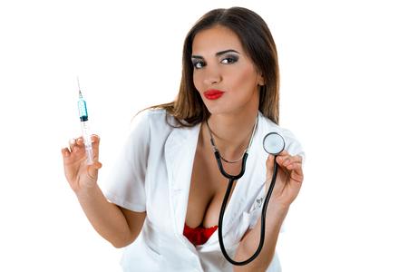 Bonita enfermera lista para controlar los latidos del corazón de un paciente con un estetoscopio y darle una inyección. Aislado en un fondo blanco.