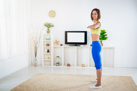 Fit young woman warming up while doing stretching exercises at home in front TV. Looking at camera.