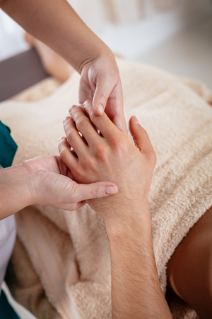 Close-up of a hads of young female therapist massaging young man's hand at beauty salon.