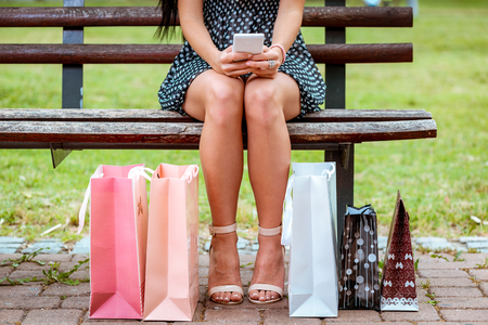 Close-up of a woman legs sitting on the bench in the park and surfing on a smarthphone with shopping bags next to.