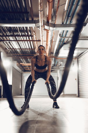Muscular young woman exercising with ropes at the garage gym. Selective focus.