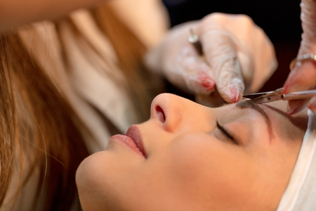 Close-up of a beautician hands applying permanent eyebrow makeup to model.