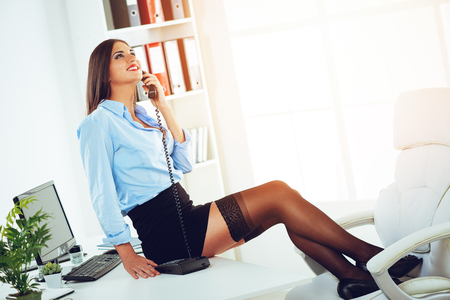 Young smiling sexy business woman sitting on the office, relaxing with her legs on the chair, and phoning. Stockfoto