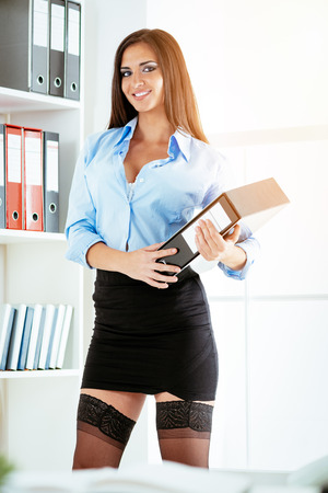 Young smiling business woman in a short skirt standing in front of shelves, holding a binder and looking at camera. Stockfoto
