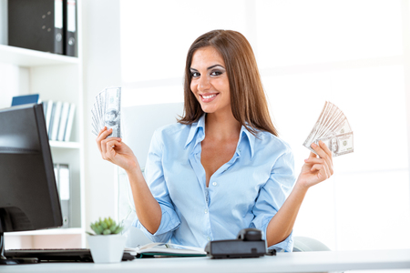 Young businesswoman in office, sitting at the office desk, holding money and with an expression of happiness on her face looking at the camera.