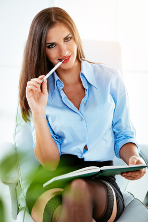 Young smiling sexy business woman in short skirt, sitting at the office holding the planner and pencil in her mouth. Looking at camera.