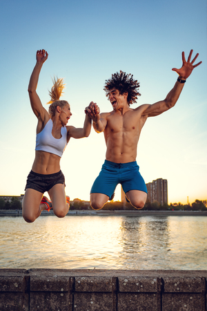 Beautiful young couple smiling and jumping after successful training by the river in the sunset.
