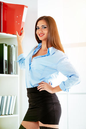 Young smiling business woman standing in front of shelves with binders and looking at camera.