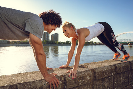 Young happy smiling couple runners training outdoors doing stretching exercise on the wall by the river.
