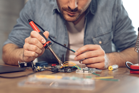 Engineer or technician focused on repair electronic circuit board with soldering iron. Reklamní fotografie