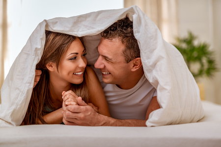 Beautiful young loving couple looking each other with love and having lazy morning in bed covered with blanket. Stock Photo