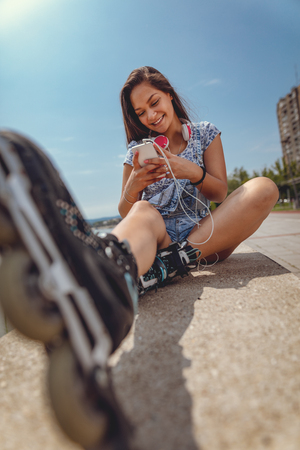 Cute smiling young Filipino woman surfing on internet or typing message on smartphone. She is sitting with roller skates and enjoying on city riverbank at the beautiful summer day. Stock Photo