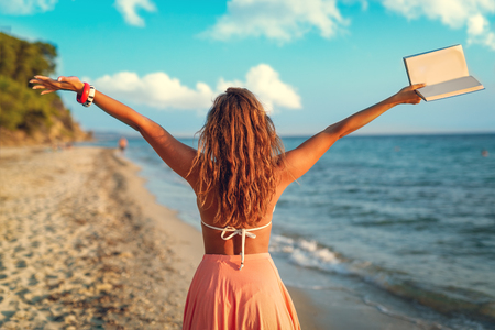 Rear view of a beautiful young woman enjoying on the beach with book in her open arms.