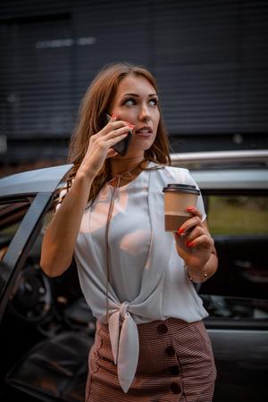 Una joven y bella mujer está hablando por el teléfono inteligente con una taza de café y va a entrar en el automóvil.