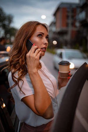 A young beautiful woman is talking on the smartphone holding a cup of coffee, and is going to enter in the car.