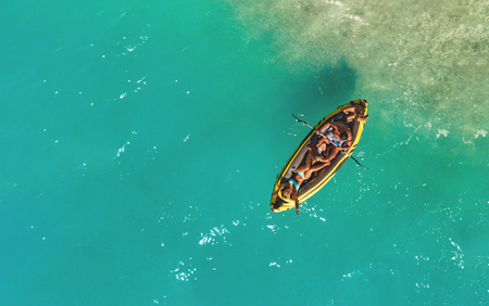 A happy family having fun in a inflatable rubber boat near the sea beach. Beautiful natural background at the summer time from air. Stock Photo - 106607233