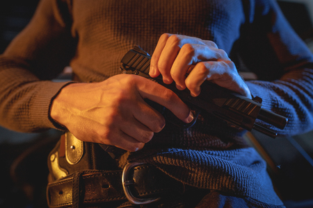 Close-up on a hands of a man carrying a gun with a bullet in the chamber, prepare to use to rob or kill someone.