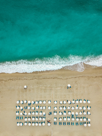 Aerial view of the amazing idyllic empty beach with white umbrellas and blue sunbed.