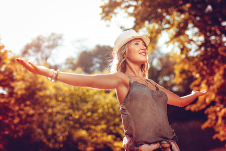 Happy young woman with open arms enjoying in the nature in early autumn sunny day.
