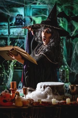 不気味な環境でひどく顔を持つ魔女と魔法の飲み物のスモーキーな緑の背景の読書レシピは悪を送ります。ハロウィーンのコンセプト。 写真素材 - 107134158