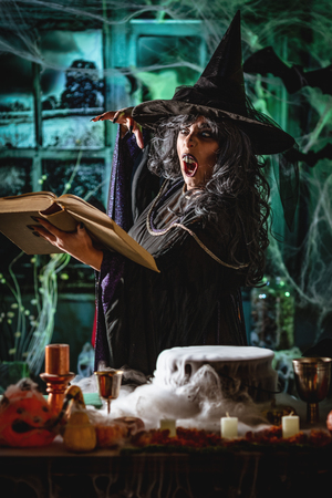Witch with awfully face in creepy surroundings and smoky green background reading recipe of magic drink sends evil. Halloween concept. 写真素材