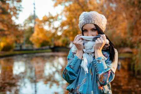 Young woman walking near the lake in a city park in a wonderful autumn day. She is tucking a shawl. Stock Photo