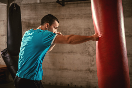 Young muscular man punching a boxing bag on cross fit training at the gym.