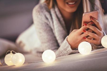 Linda joven sonriente con smarthphone y sonriendo durante las acogedoras vacaciones de Navidad en casa. Foto de archivo