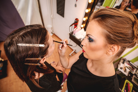 Pretty young woman having make-up applied by a makeup artist. Close up.