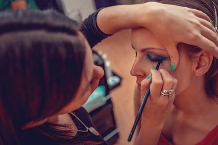 A portrait of a pretty woman having make-up applied by a makeup artist. Close-up.