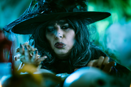 Witch with awfully face in creepy smoky green surroundings full of cobweb is reading recipe of magic drink. Halloween concept. Zdjęcie Seryjne