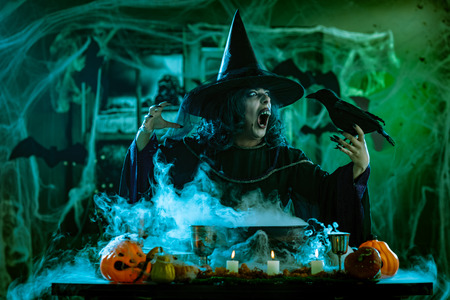 Witch with awfully face in creepy surroundings and blackbird in her hand send messages to dead. Halloween concept.