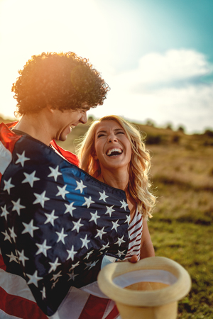 Happy young couple enjoys a sunny day in nature. Theyre hugging each other, wrapped in american flag.