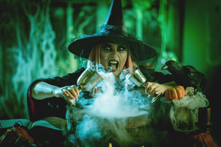 A witch in foggy surrounding holds two goblets above boiling water for a cooking poison soup.